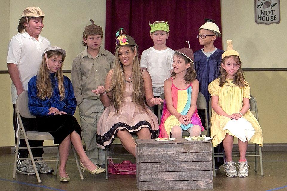 7 children are sitting with costumes and rehearsing play