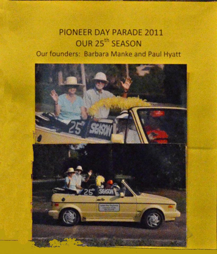 Founders Barbara Manke and Paul Hyatt sitting in little convertible yellow car driving through parade