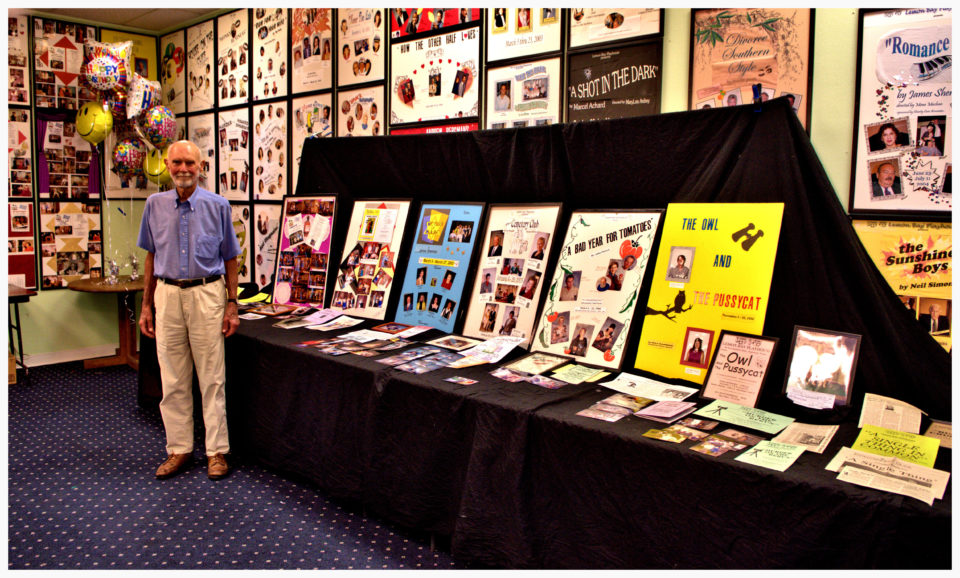 man standing in room full of show posters