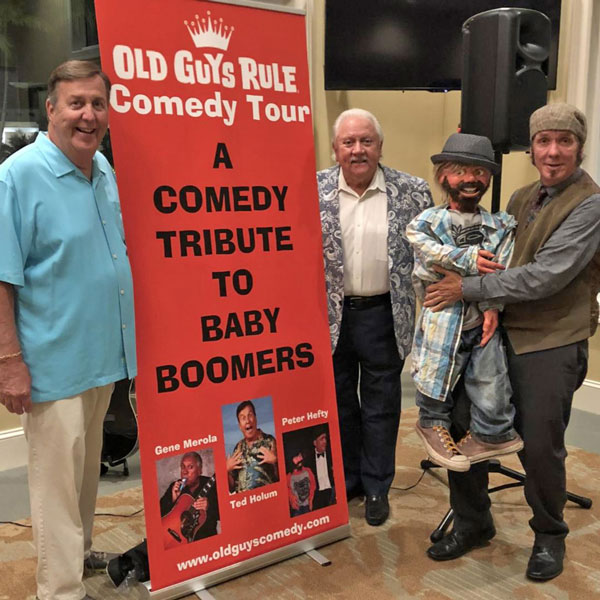 Three middle-age men standing next to sign advertising Old Guys Rule Comedy Tour - A Comedy Tribute to Baby Boomers